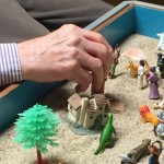 A residents hand placing an item in the sand tray.