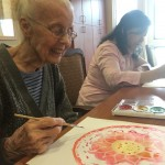 Donna smiling while putting the finishing touches on her beautiful Mandala.