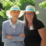 Gayle and Julie wearing matching summer hats and enjoying the sunshine on the patio.