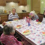 A group of residents enjoying hot dogs and hamburgers for this 4th of July luncheon.