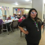 Jocelyn serving residents wearing her red, white and blue glasses.