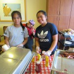 A couple of happy volunteers working hard as part of the assembly line to prepare the plates of food.