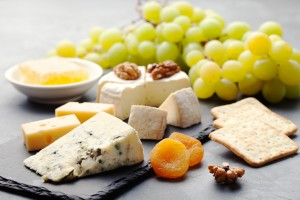 Glass of white wine and assorted cheese with grape on a stone and slate background Copy space